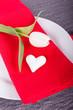Teller mit weißer Tulpe, Herz und roter Serviette
