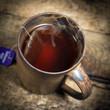 Tasse mit schwarzem Tee auf einem alten Holztisch