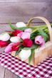 Körbchen mit Tulpen auf rustikaler. karierter Decke