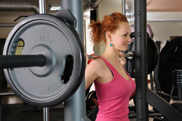 young girl doing squats with barbell