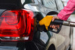 Woman filling up car at petrol station, black car - 64231540