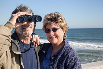 Retired couple on beach vacation with Binoculars