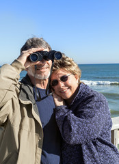 Retired couple on beach vacation with binoculars hugging