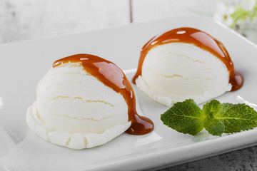 white ice cream ball on a plate with caramel