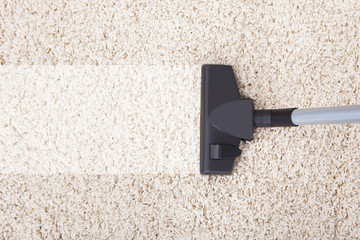 Vacuum Cleaner On Rug At Home