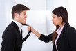 Angry Businesswoman Holding Businessman's Tie