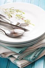 A stack of clean white plates with sliverware