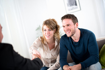 cheerful young couple with salesman at home