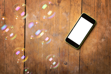 Smartphone and bubbles on wooden surface