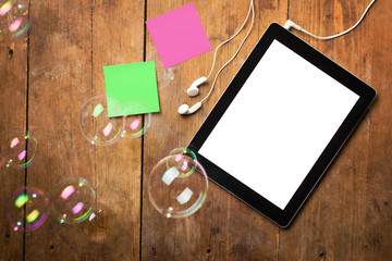 Tablet, earphones, sticky notes and bubbles on wooden surface