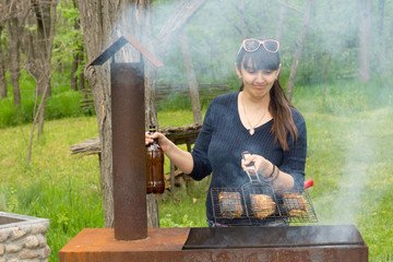 Attractive woman cooking over a picnic BBQ