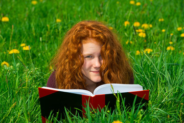 red-haired girl in the spring- meadow is reading