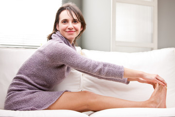 girl doing stretching exercises on her sofa
