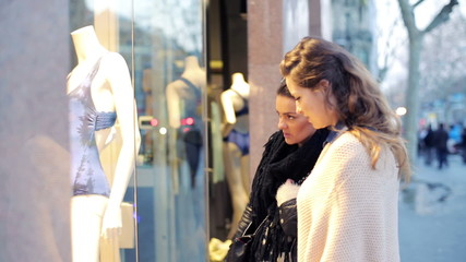 Girlfriends looking at bikini on shop display in the city