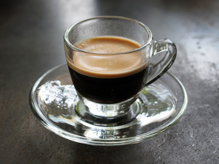 Small glass of espresso coffee on table