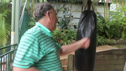 Middle aged man works out with a punching bag.