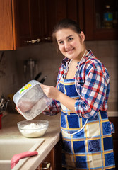 smiling housewife interspersing flour from bowl