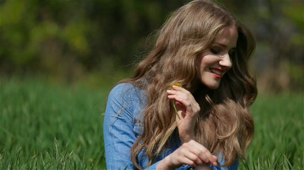 Happy woman sourranded by grass picking yellow flowers