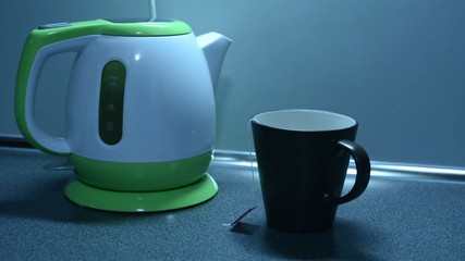 Boil water in a kettle and pouring tea on the kitchen counter