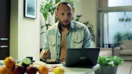 Young man eating breakfast and surfing net on laptop at home