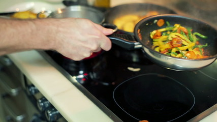 Cook flipping vegetables on frying pan in the kitchen