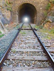 railway with light at the end of the tunnel.
