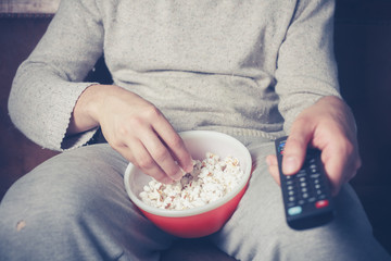 Young man watching television and eating popcorn