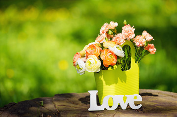 Love decoration sign and a bunch of spring flowers