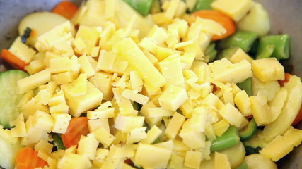 Preparing vegetable mix with pieces of cheese