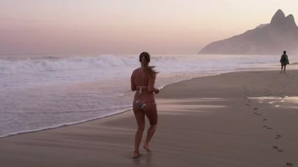 Молодая женщина бегает по береговой линии