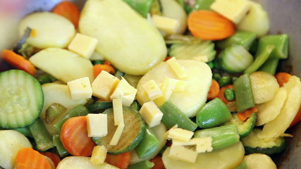 Placing pieces of cheese on vegetable mix