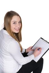Junge Frau schreibt auf ein Klemmbrett