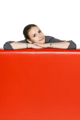 Woman leaning on the red leather couch