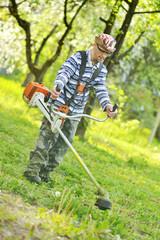 jardinier maniant une tondeuse à essence
