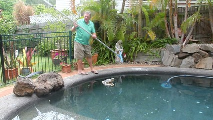 Man walks in with long brush to clean salt in his swimming pool.