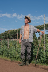sexy farmer guy in vegetable garden with shovel