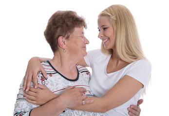 Generation: Enkeltochter mit der Oma - lachend Arm in Arm
