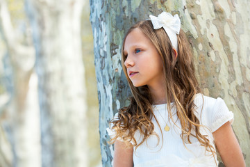 Girl in white standing next to tree.