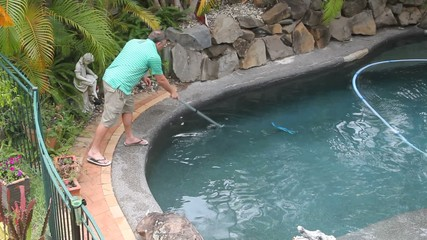 Man cleans pool with long scraper and automatic pool cleaner.
