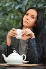 Young woman drinking tea at sidewalk cafe