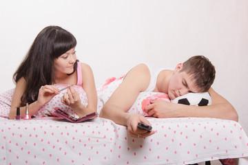 wife looks at her husband sleeping football fan