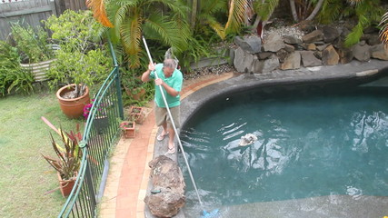 Man walks around with long brush to clean the corner of pool.