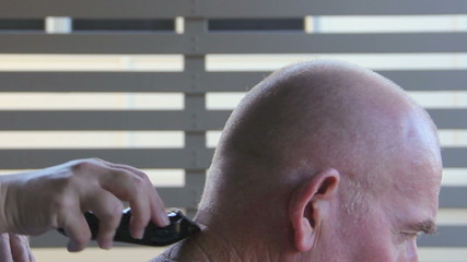 Elderly man getting his neck trimmed with a trimmer.