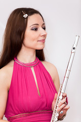 Portrait of flutist woman in red dress with silver flute