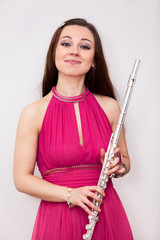 Woman fluist with silver flute looking at camera