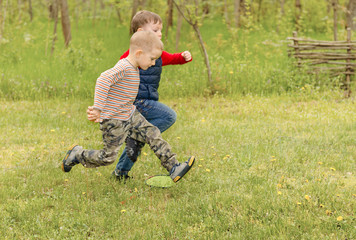 Two small boys running across a field