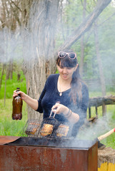Smiling woman cooking outdoors over a BBQ