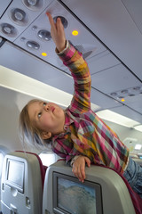 Little blonde girl playing at Qatar Airways plane