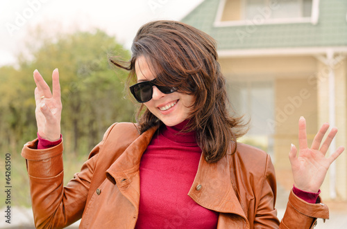Vivacious beautiful woman outside a house