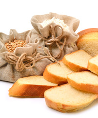 Wheat grains and flour in the cloth sacks and fresh bread pieces
